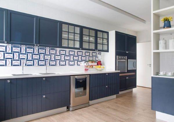 Cozinha azul com bancada de quartzo e revestimento geométrico