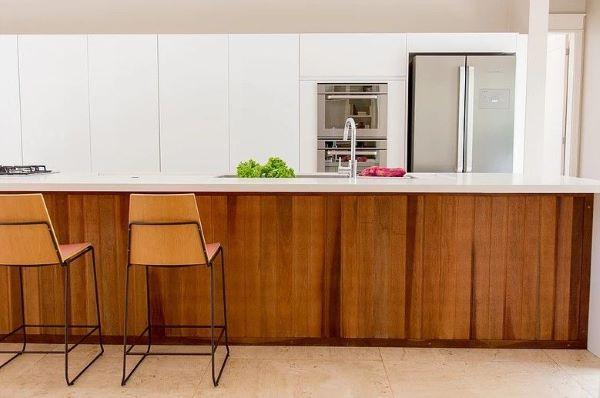Cozinha branca com bancada de madeira e superfície de quartzo branca