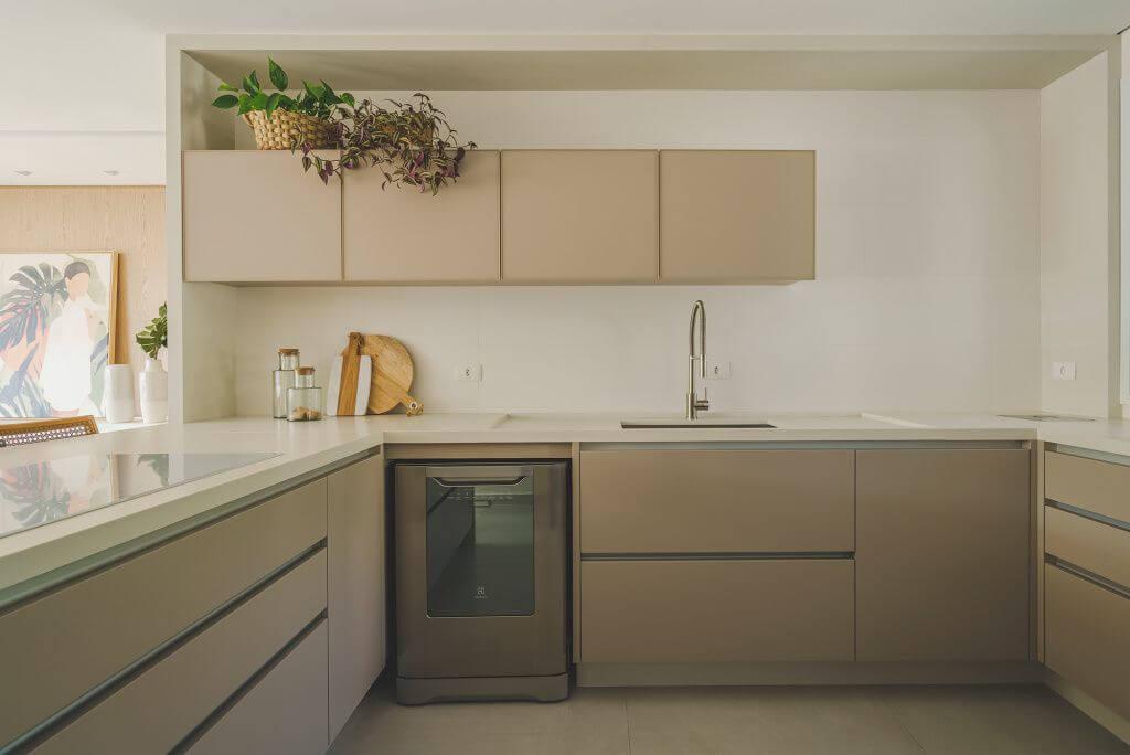 Cozinha com armários bege e bancada de quartzo branco