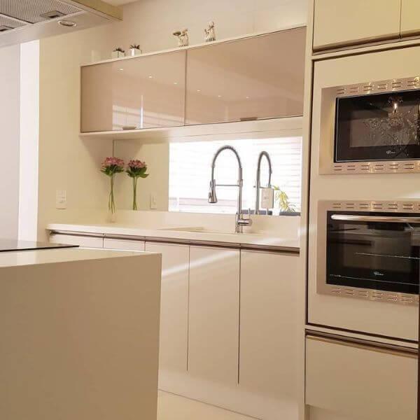 Cozinha com bancada de quartzo branco e armários da mesma cor