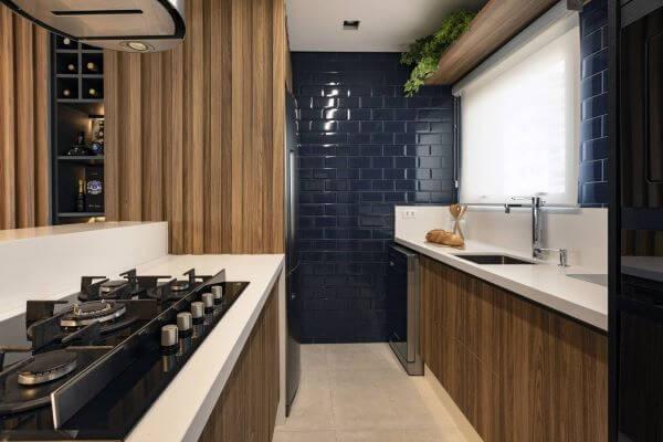 Cozinha com revestimento azul e bancada de quartzo branca