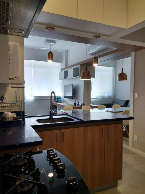 Cozinha integrada com a sala dividida pela bancada de quartzo preto