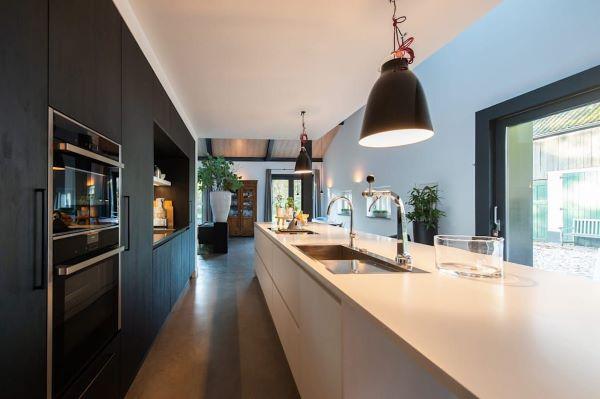 Cozinha luxuosa com bancada de quartzo branco e armários pretos planejados