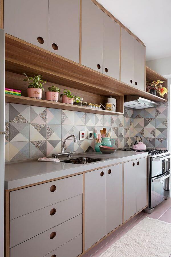 Cozinha moderna com bancada de quartzo cinza e revestimento geométrico na parede