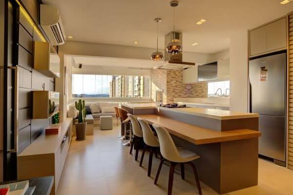 Decoração conceito aberto com bancada de quartzo branco e mesa de madeira