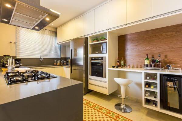 Decoração de cozinha em u com bancada de quartzo marrom e móveis planejados