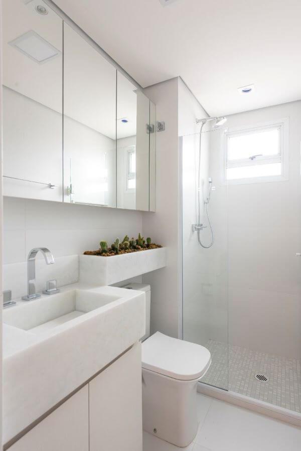 Banheiro com bancada de quartzo branco e espelheira