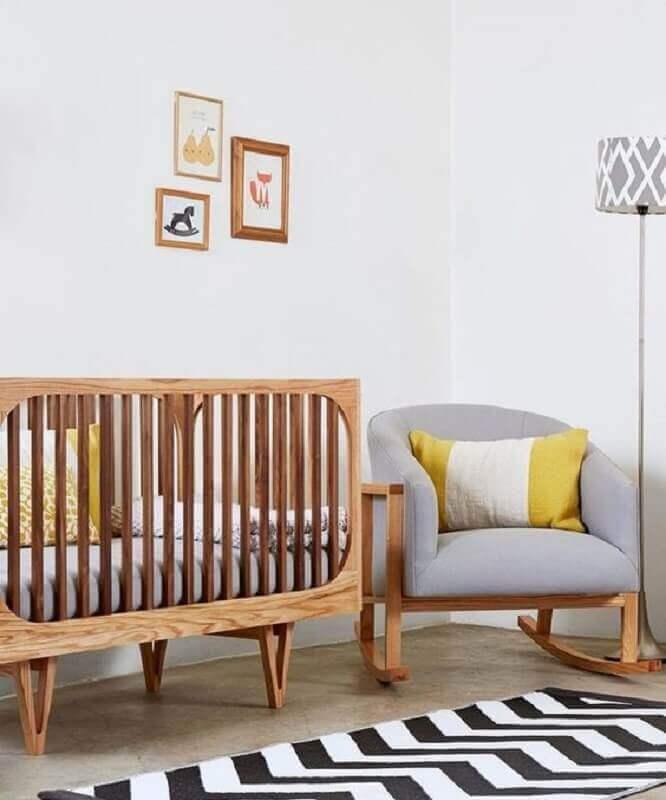 Decoração clean para quarto de bebê com poltrona cinza e berço de madeira Foto Love Property