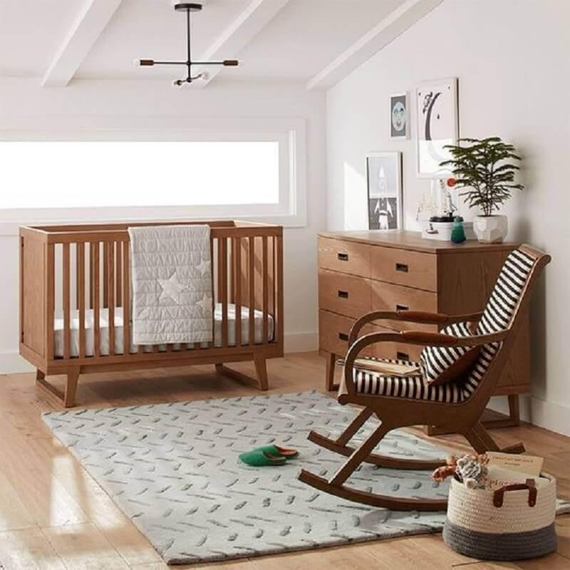 Quarto de bebê simples decorado com cadeira de balanço e berço de madeira Foto Crate and Barrel