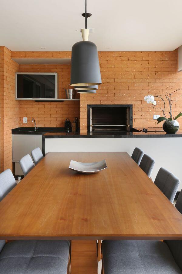 Área de churrasqueira pequena com revestimento de tijolinho e moveis de madeira modernos