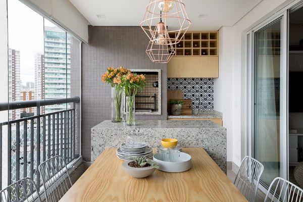 Churrasqueira pequena embutida na varanda gourmet com balcão de granito cinza e mesa de madeira na decoração