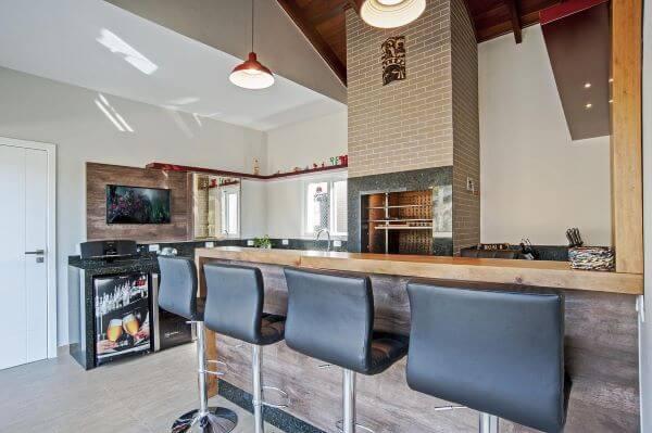 Churrasqueira pequena na área de lazer moderna com balcão de madeira e banquetas preta