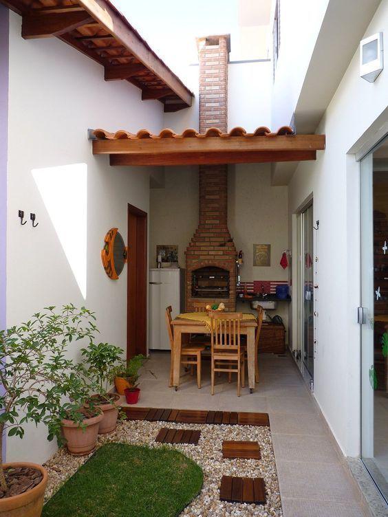 Quintal pequeno com espaço para churrasqueira pequena de tijolo e mesa de madeira com 4 lugares