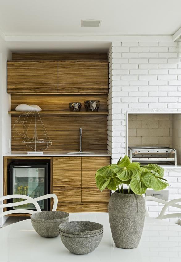 Churrasqueira pequena revestida com tijolinho branco moderno e gabinete planejado de madeira