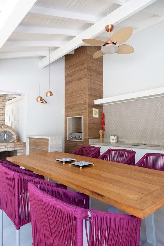 Área de lazer moderna com mesa de madeira e cadeiras cor de rosa e churrasqueira pequena no canto