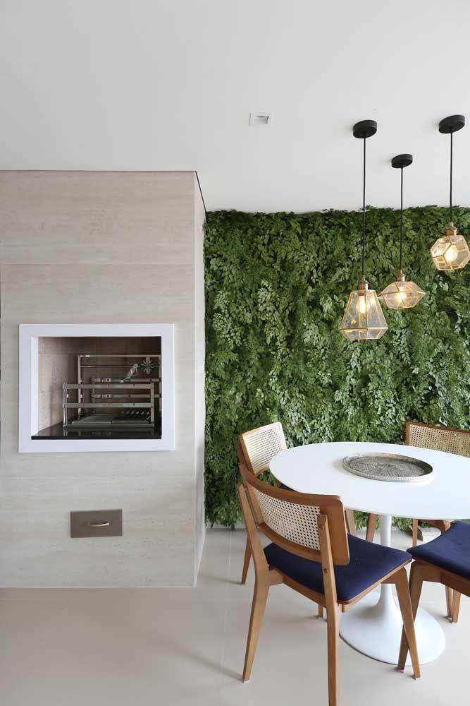 Varanda com churrasqueira pequena e jardim vertical na decoração moderna