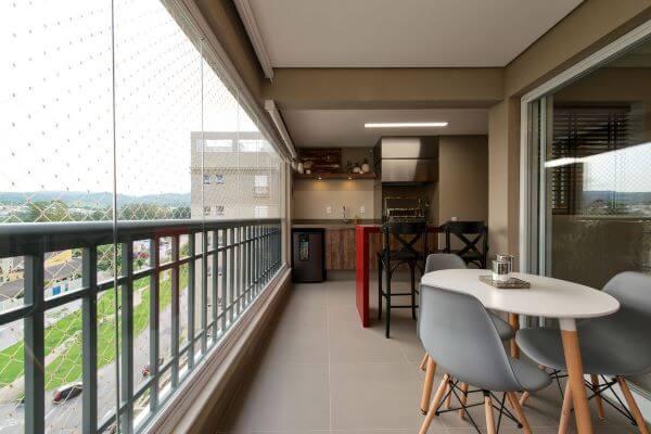 Varanda de vidro com área de churrasqueira pequena e moveis confortáveis