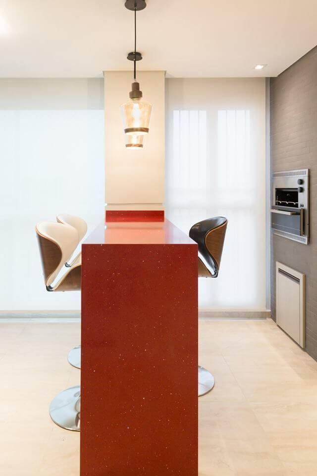 Área de churrasqueira pequena com bancada vermelha e banquetas modernas