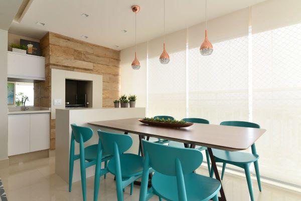 Varanda gourmet com churrasqueira pequena revestida com porcelanato claro e mesa de madeira com cadeiras azuis modernas