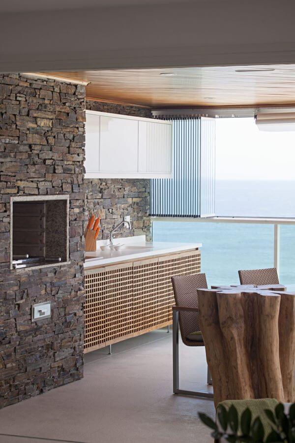 Área gourmet rustica com mesa de tronco com churrasqueira pequena