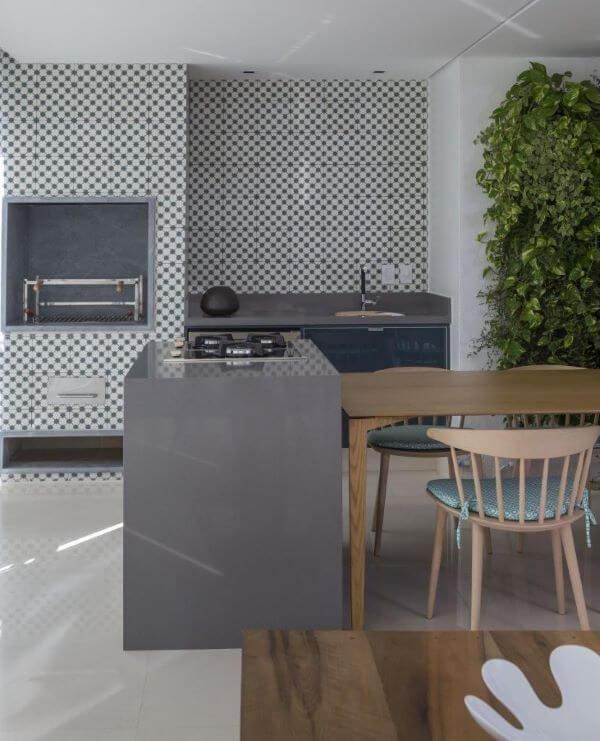 Área gourmet com churrasqueira pequena e jardim vertical na decoração