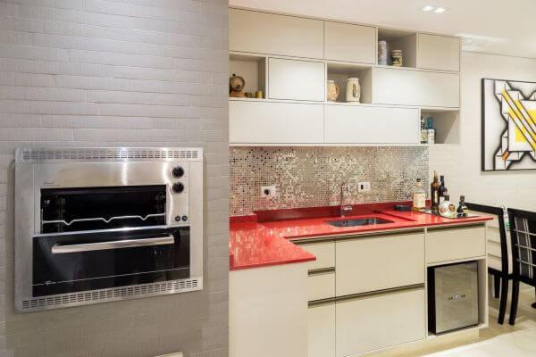Área gourmet com churrasqueira pequena e cozinha com bancada vermelha moderna