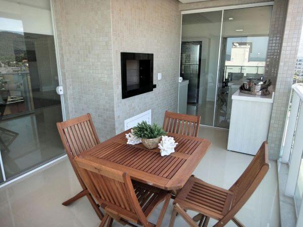 Área gourmet com churrasqueira pequena e conjunto de mesa e cadeiras de madeira