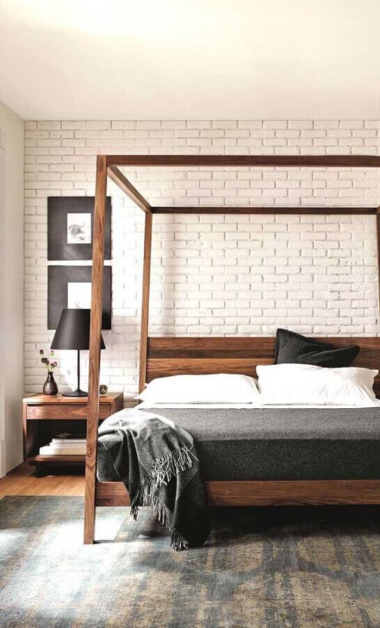 Cama com dossel de madeira para quarto de casal decorado com parede tijolinho branco Foto DecoRecent