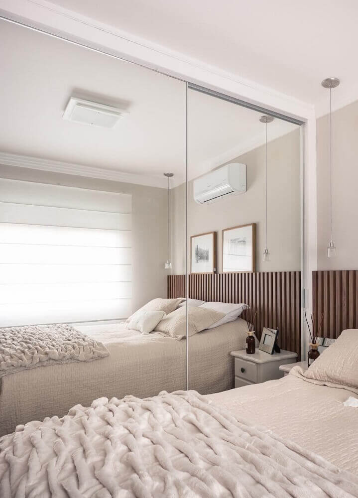 quarto de solteiro com cabeceira de madeira e guarda roupa grande com espelho Foto Webcomunica