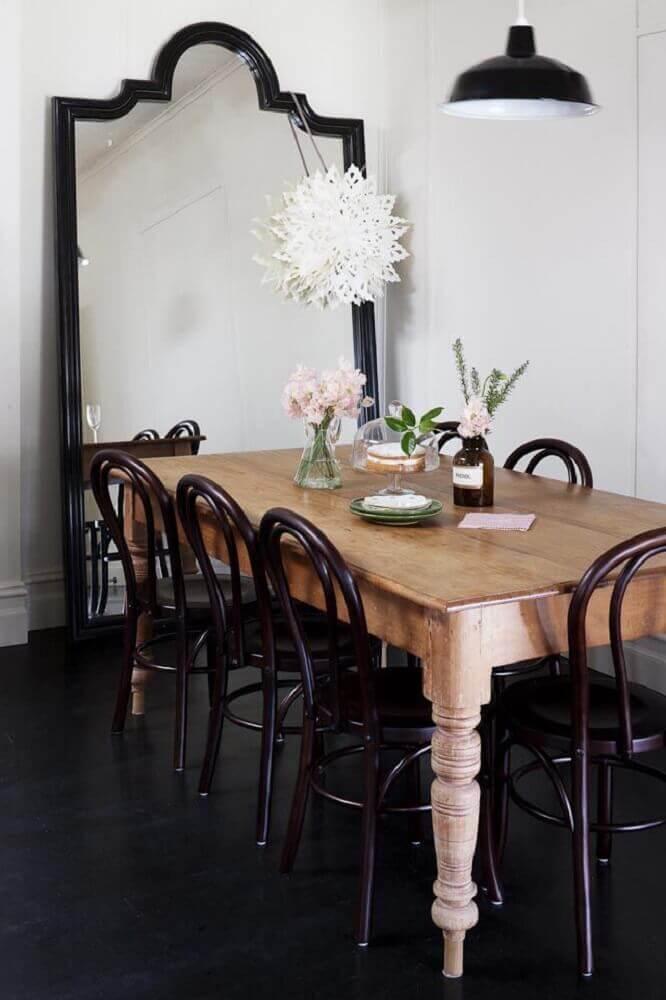 Sala de jantar decorada com mesa de madeira e espelho grande com moldura preta - Foto: Apartment Therapy