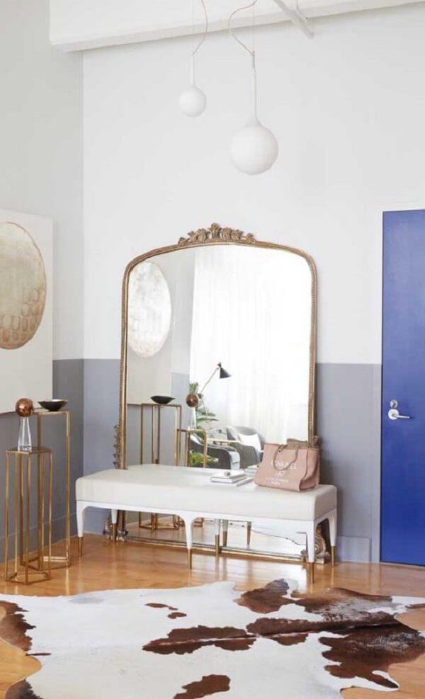 Espelho grande com moldura dourada decora ambiente. Fonte: Carousell