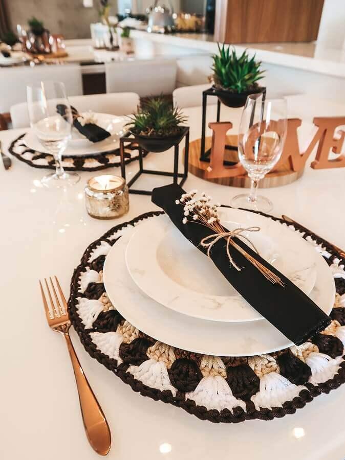 Mesa posta preta e branca decorada com sousplat de crochê Foto Circulo