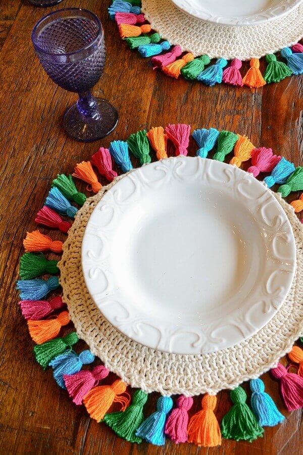 Decoração de mesa de madeira com sousplat de crochê colorido Foto Circulo