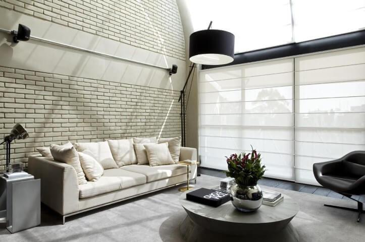 Loft com parede de tijolo pintada de cor clara Projeto de Diego Revollo
