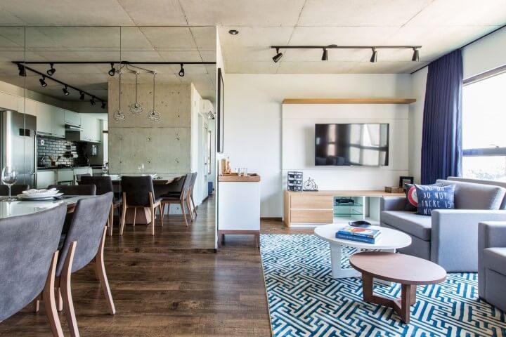 Loft com parede espelhada em sala integrada Projeto de Fabiana Montandon