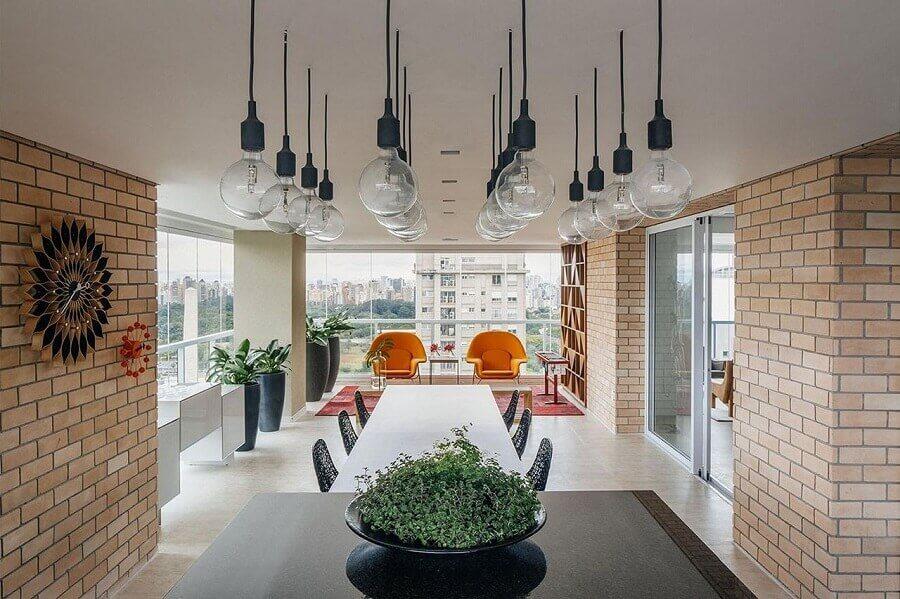 Parede de tijolinho e luminária pendente para decoração de varanda de apartamento grande Foto FCstudio