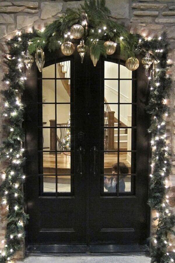 varanda decorada com luzes de natal e enfeites dourados Foto Divian Arts