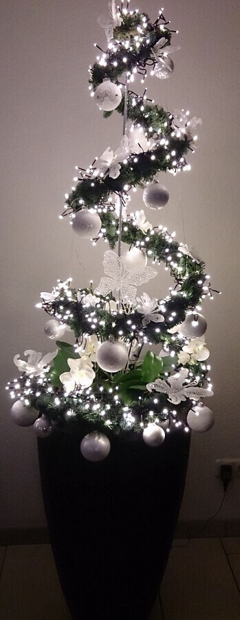 vaso de plantas decorado com luzes de natal Foto GoodNewsArchitecture