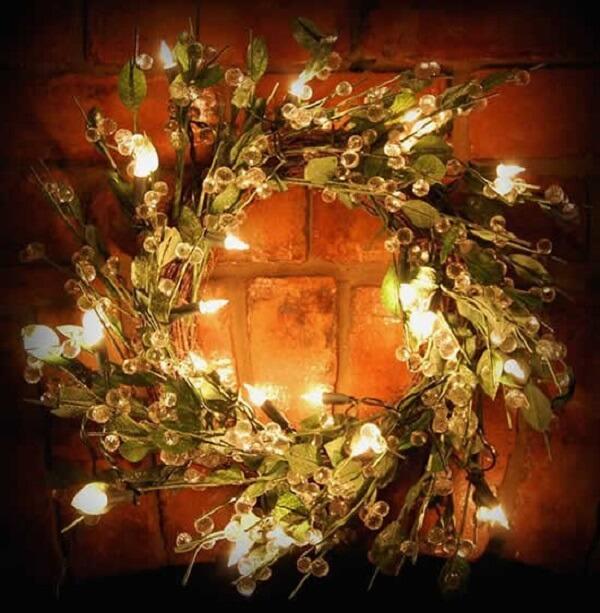 Coroa com folhas artificiais e luzes de natal