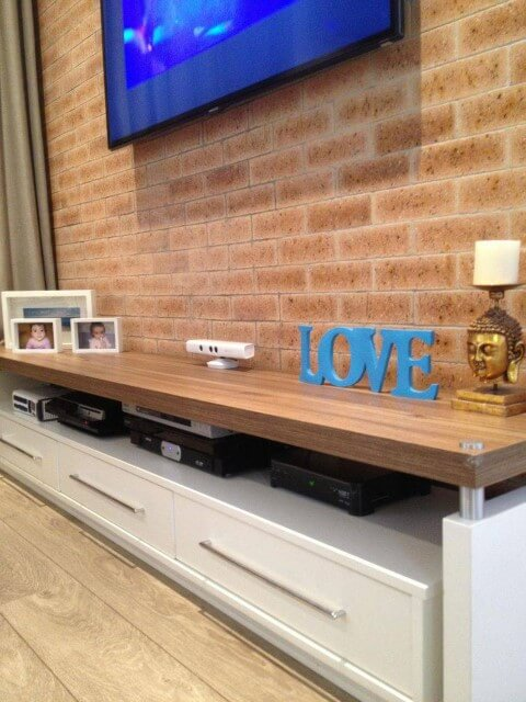Sala de estar com papel de parede 3D de tijolinhos Projeto de Adriana Victorelli