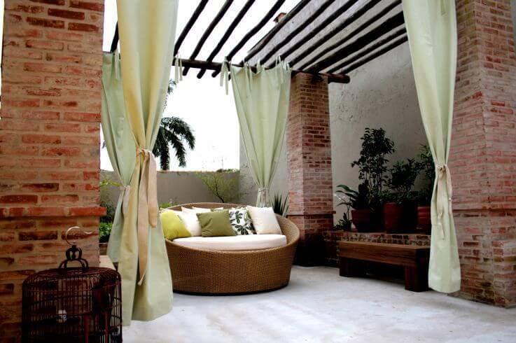 Varanda com puff redondo com assento branco Projeto de Joel Caetano Paes